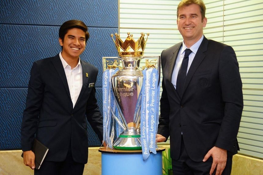 Malaysia's Sports Minister Syed Saddiq (left) and Manchester City's Spanish Chief Executive Officer Ferran Soriano posing for a picture with the English Premier League trophy in Putrajaya, on May 23, 2019.