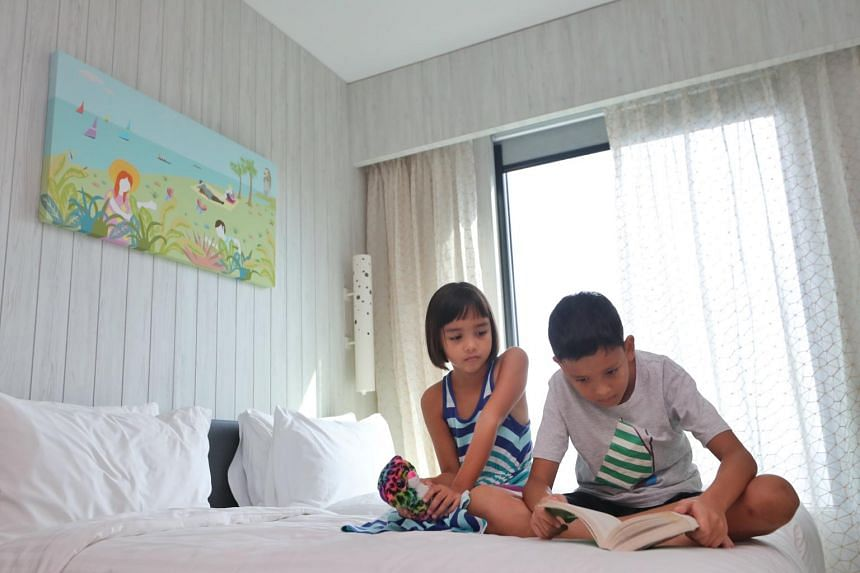 Micah broom and Leah broom reading a book together in the hotel room.