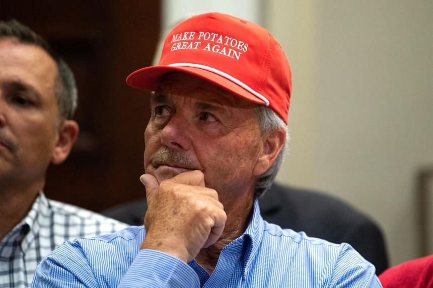 A farmer wears a President Donald Trump themed hat listens as he delivers remarks on supporting American farmers, in the Roosevelt Room at the White House in Washington, on May 23, 2019.