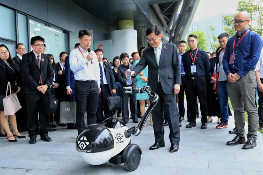 Deputy Prime Minister Heng Swee Keat interacting with a robot while touring artificial intelligence hub Zhangjiang International Innovation Harbour in Shanghai on May 25, 2019.