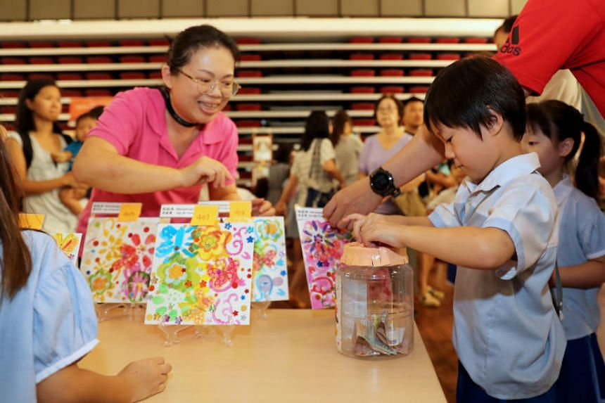 """Singapore Hokkien Huay Kuan Pre-school teacher Cheng Rong Tao looks on as student Quek Rui Yang contributes to an artworks sale as part of the school's annual """"Start Small Dream Big"""" Dragon Boat Festival celebrations."""
