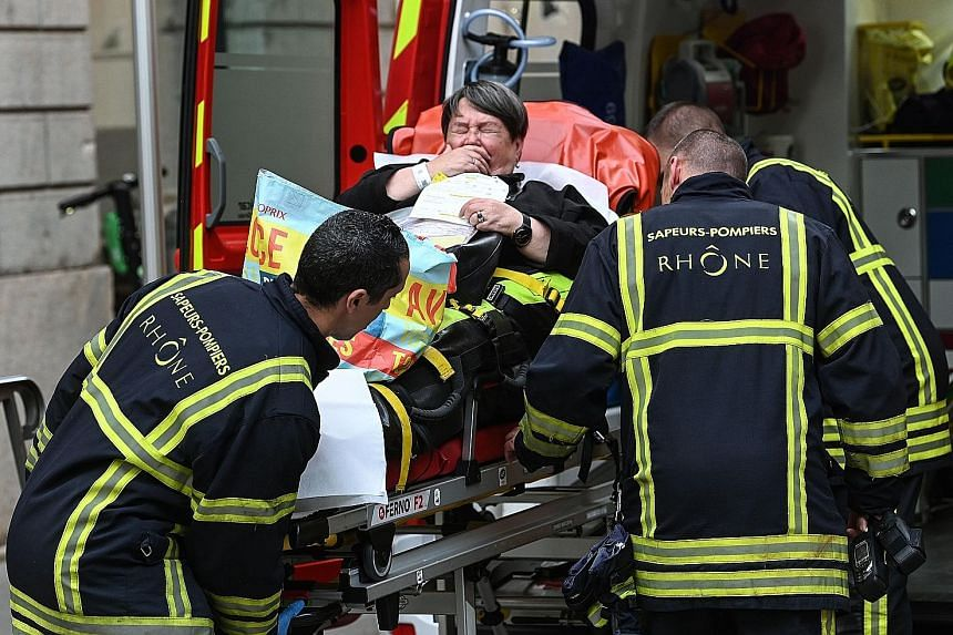 Emergency workers attending to a woman after a suspected package bomb blast in the heart of Lyon, south-east France, on Friday. PHOTO: AGENCE FRANCE-PRESSE