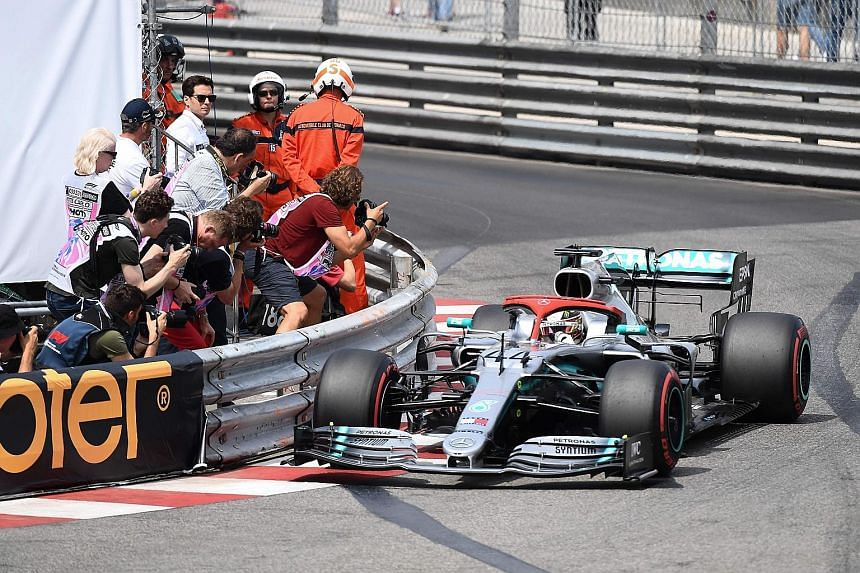 Mercedes driver Lewis Hamilton going past a posse of press photographers during the qualifying session for the Monaco Grand Prix yesterday. He pulled off a record lap to clinch pole position ahead of teammate Valterri Bottas for today's race.