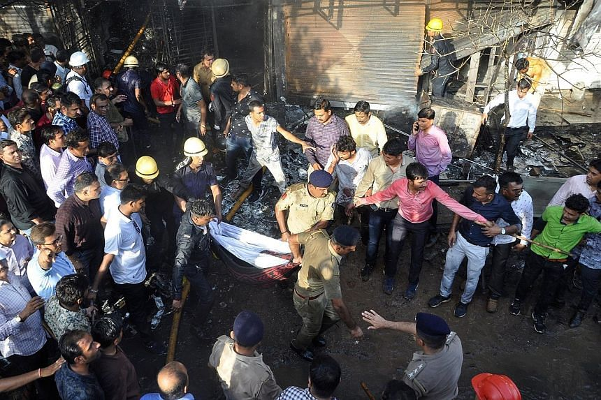 Firefighters and police removing a body from a building housing an illegal tuition centre that caught fire in Surat, in India's Gujarat state, on Friday. Sixteen of the dead were young women who had been preparing for exams at the tuition centre.
