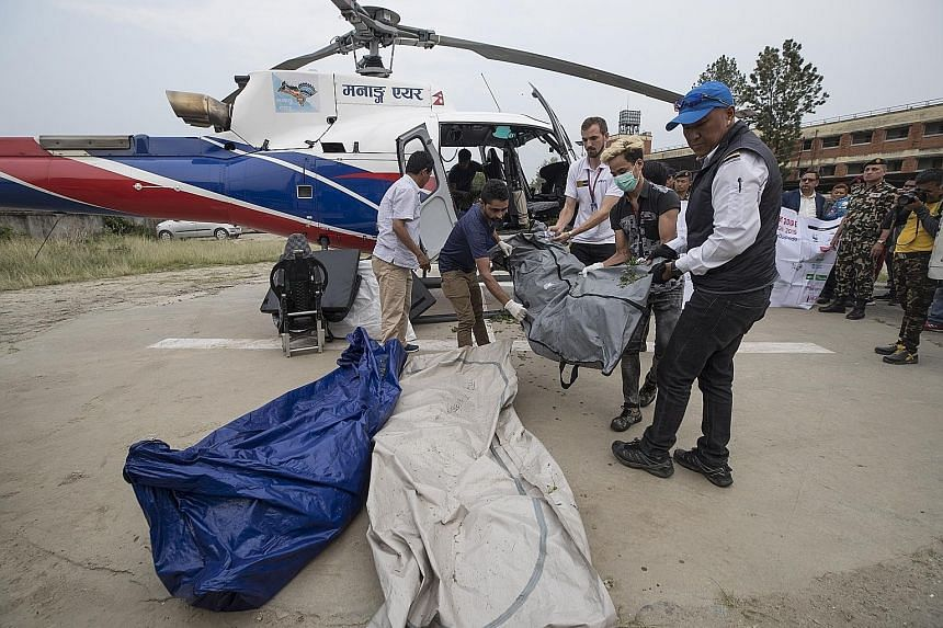 Nepalese trekking staff and policemen unloading the bodies of four unidentified climbers at a helipad of a hospital in Kathmandu last week. These were the bodies of climbers who died on Mount Everest in previous years and were found this year. The cl