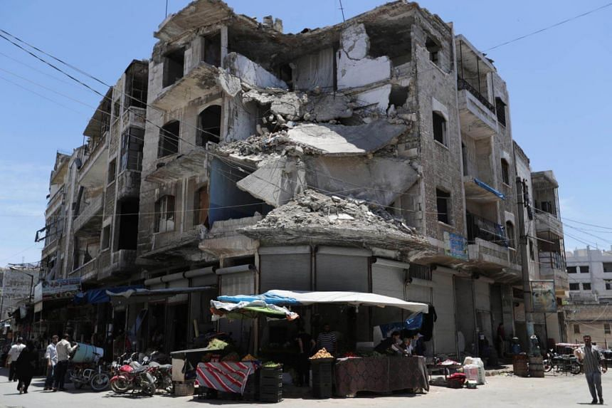 People walk past a damaged building in the city of Idlib, Syria.