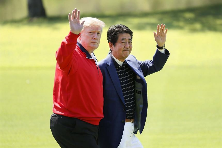 US President Donald Trump, dressed in a red pullover, and Japan Prime Minister Shinzo Abe, wearing a blue blazer and white pants, smiled for photographers before taking off for their game.