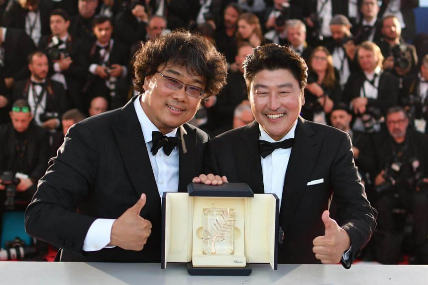 South Korean director Bong Joon-Ho (left) with South Korean actor Song Kang-ho after winning the Palme d'Or, the top award at the Cannes Film Festival, for the film Parasite on May 25, 2019.