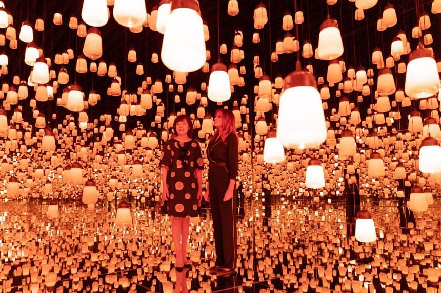 US First Lady Melania Trump (right) and Akie Abe, wife of Japan's Prime Minister Shinzo Abe, look at the Forest of Resonating Lamps installation during a visit to the Mori Building Digital Art Museum in Tokyo, on May 26, 2019.