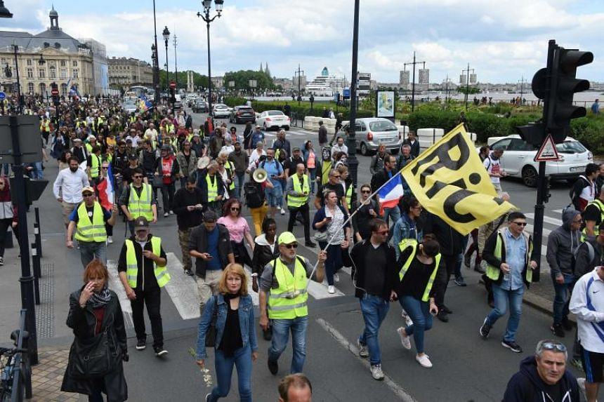 A protester holds a flag with bearing the acronym RIC (Citizens' Initiative Referendum) during an anti-government demonstration called by the Yellow Vests movement on May 25, 2019, in Bordeaux, southwesten France.