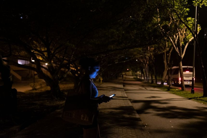 Dolly Vargas Salles, 40, a fellow trail runner and maid from the Philippines, checking her phone after work.