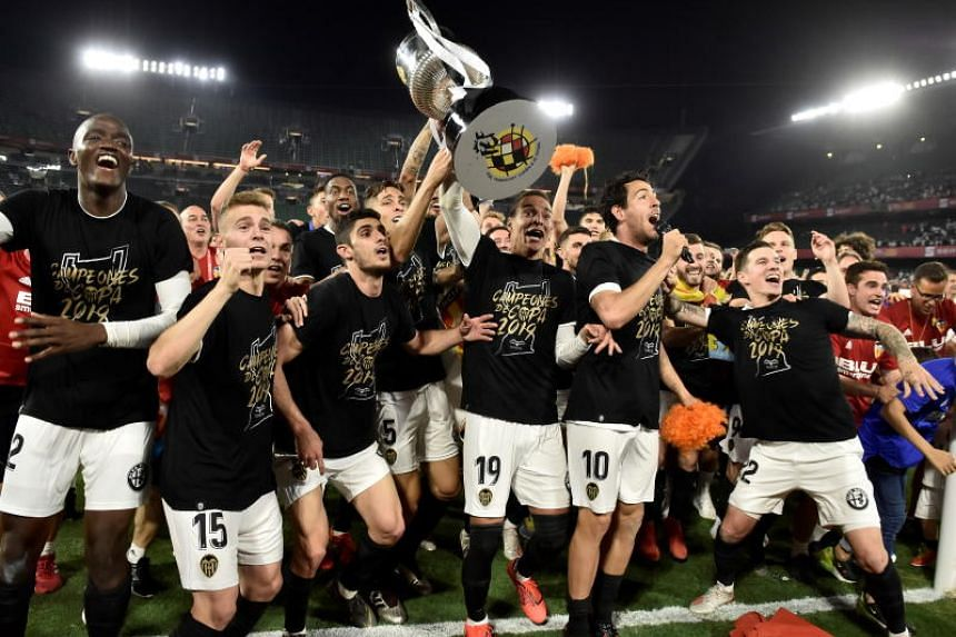Valencia's players celebrate after defeating Barcelona in the King's Cup final at the Benito Villamarin stadium, in Seville, southern Spain, on May 25, 2019.