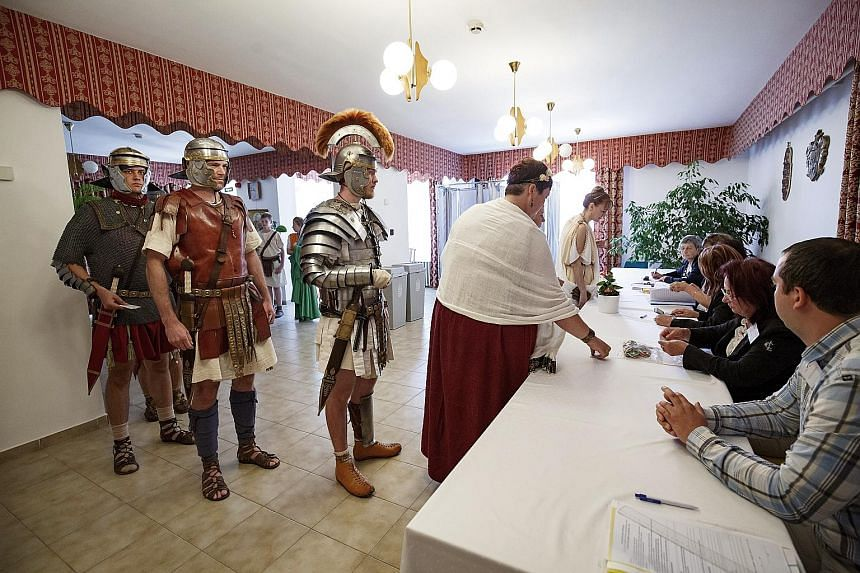 Colonia Rostallo Cultural and Military History Foundation members in ancient Roman legionary costumes at a polling station in Hungary yesterday.
