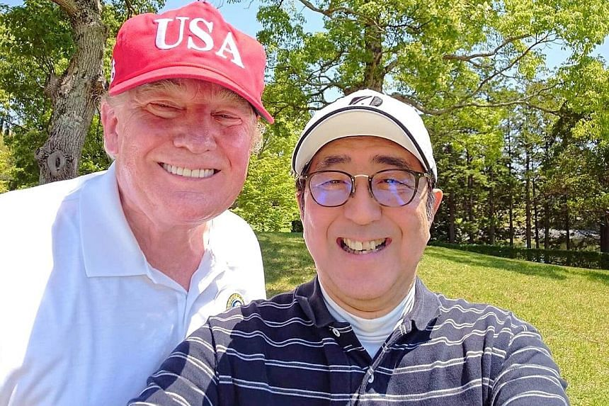 "Mr Trump and Mr Abe taking a selfie at Mobara Country Club in Japan's Chiba prefecture yesterday. Mr Abe said he hoped to make the Japan-US alliance ""even more unshakeable"". US President Donald Trump and First Lady Melania Trump, flanked by Japanese"