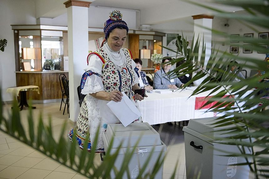 A woman in folk attire casting her ballot at a polling station in Bujak, Hungary, yesterday. The marathon election is expected to further dent traditional pro-European Union parties and bolster the nationalist fringe in the European Parliament. PHOTO