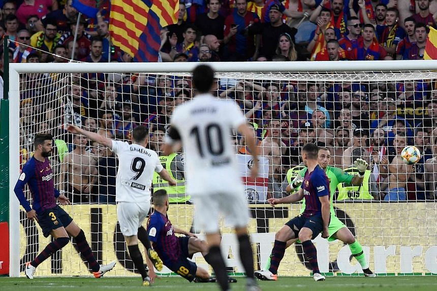 Left: Valencia chairman Anil Murthy (behind the trophy), players and coaching staff celebrating their 2-1 victory over Barcelona in the King's Cup final on Saturday. Below: Kevin Gameiro (No. 9) scoring the opener at the Benito Villamarin stadium in