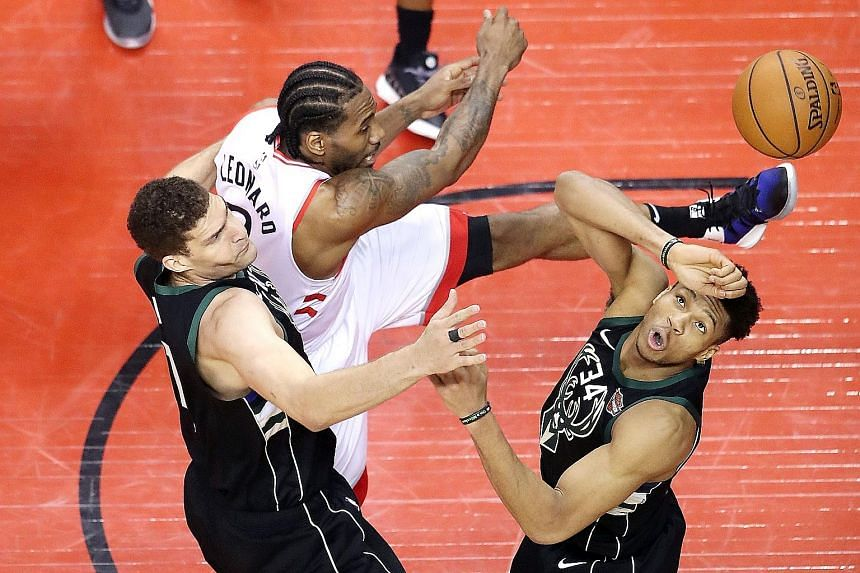"""Left: Raptors guard Kyle Lowry celebrating qualification for the NBA Finals with his sons. He described his fellow All-Star teammate Kawhi Leonard as a """"monster"""" for his several clutch plays down the stretch. Leonard battling for the ball in Game 6 o"""
