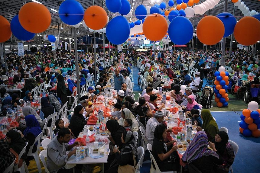 Residents of different races and religions joining their Muslim compatriots in breaking fast at Kampong Ubi Community Centre yesterday. The event, Harmony Iftar 2019, involved close to 4,000 residents from the Marine Parade cluster, with President Ha