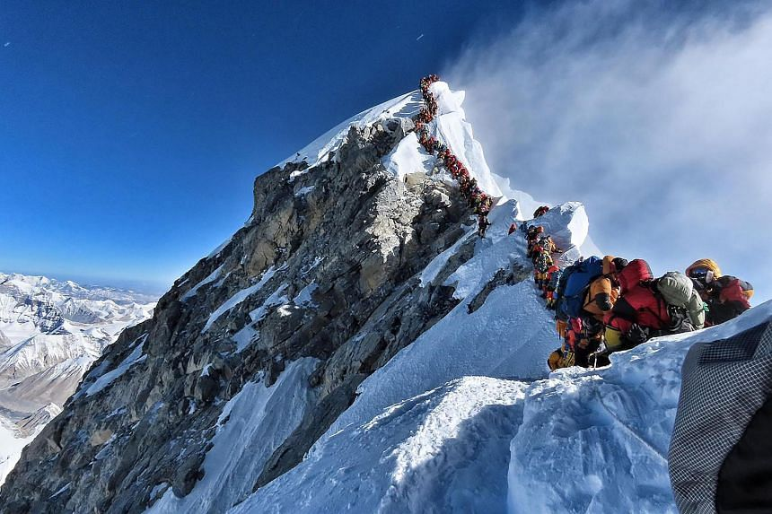 A long line of mountain climbers line up to stand at the summit of Mount Everest.