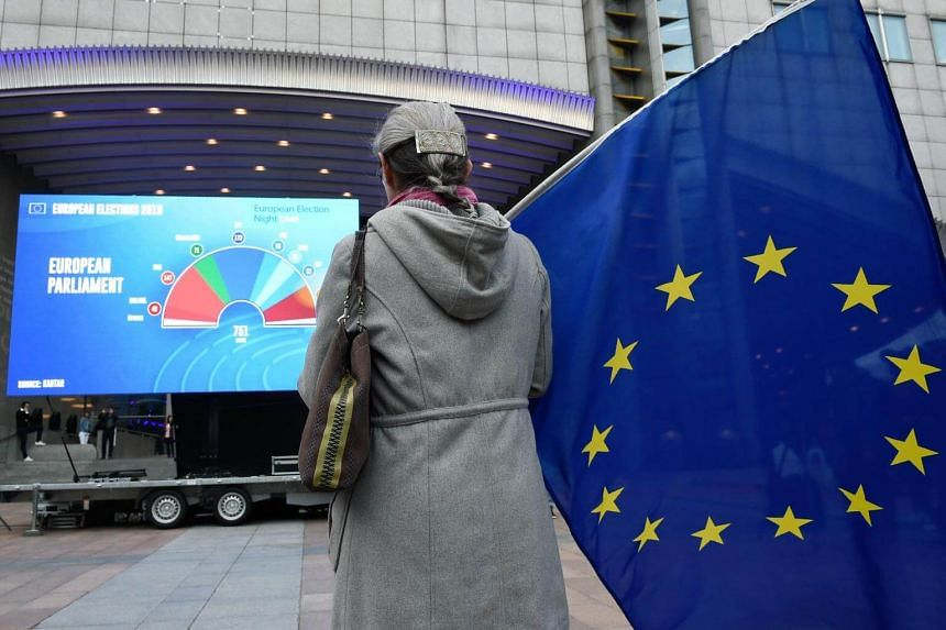 A woman holds an EU flag outside the European Parliament as people wait for the European elections results in Brussels, on May 26, 2019.