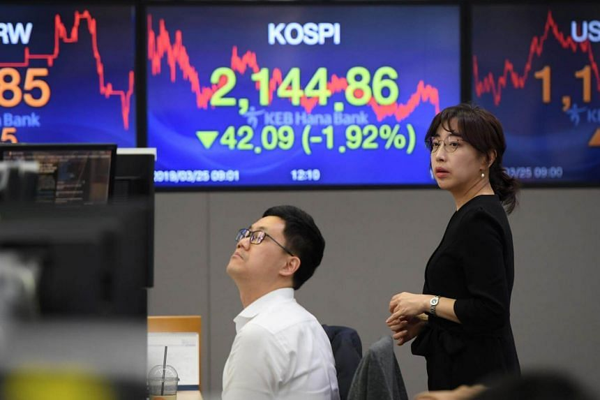 Currency dealers monitor exchange rates in front of a screen showing South Korea's benchmark stock index, at the KEB Hana Bank in Seoul, on March 25, 2019.