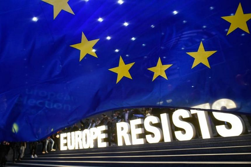 """People hold letters forming the words """"Europe Resists"""" during an action of activist group Avaaz outside the European Parliament after the announcement of results for European parliamentary elections in Brussels on May 26, 2019."""