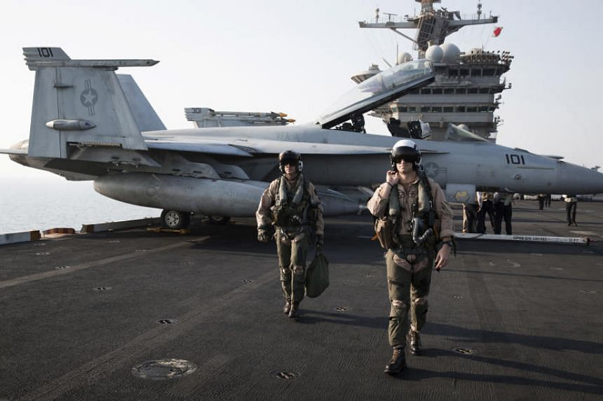 """A US Navy pilot and a weapons system officer from the VFA-11 """"Red Rippers"""" squadron after returning to the aircraft carrier USS Theodore Roosevelt in the Persian Gulf on Aug 6, 2015. The squadron began noticing strange objects just after the Navy"""