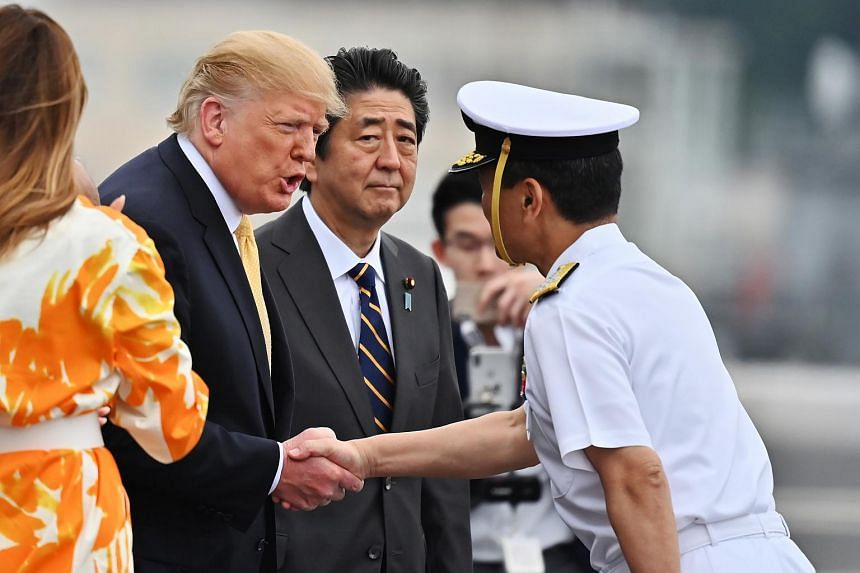 US President Donald Trump greets a naval officer while standing next to Japanese Prime Minister Shinzo Abe during a visit to the Japanese Navy destroyer JS Kaga.