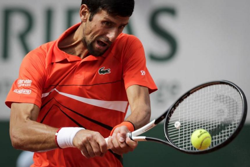 Serbia's Novak Djokovic plays a backhand return to Poland's Hubert Hurkacz during their men's singles first round match on day two of The Roland Garros 2019 French Open tennis tournament in Paris on May 27, 2019.