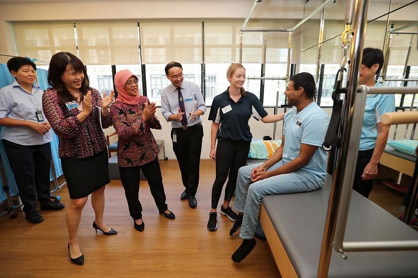 President Halimah Yacob at Abilities Beyond Limitations and Expectations (ABLE) with ABLE director Denny Lie (centre), physiotherapist Mary Wrixton and her patient Mohamad Zahir Saithu Julalutheen (second from right).