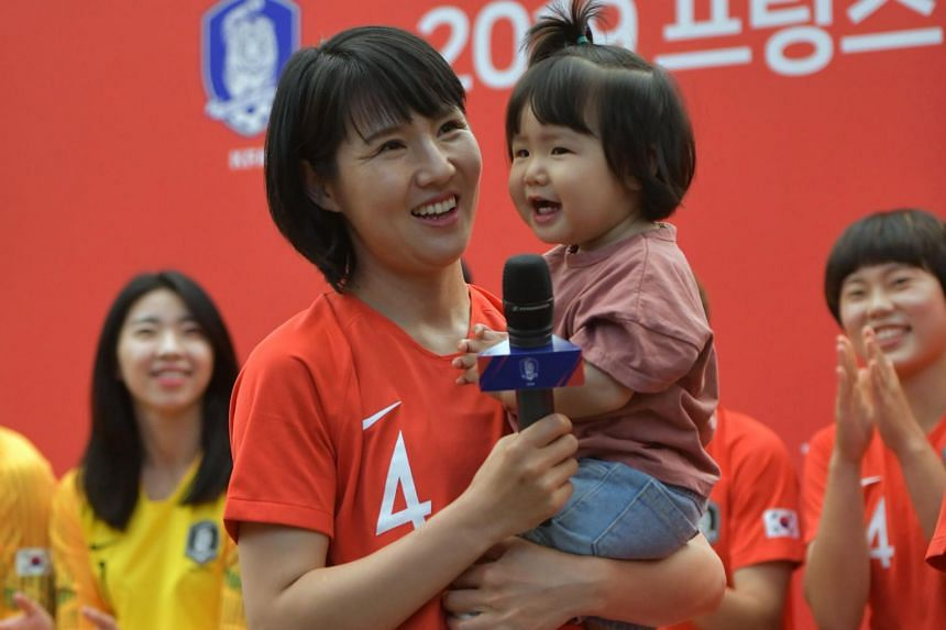 South Korean women's football team player Hwang Bo-ram (centre) holding her daughter Lee Bom during a launching ceremony of the South Korean squad for the upcoming Fifa Women's World Cup.