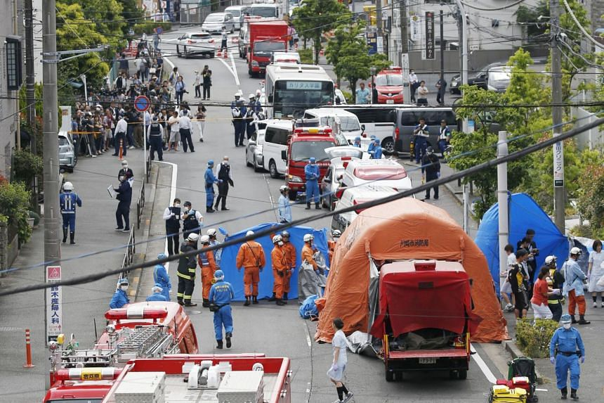 Rescue workers and police officers at the site where 16 people were injured in a suspected stabbing by a man in Kawasaki, Japan.