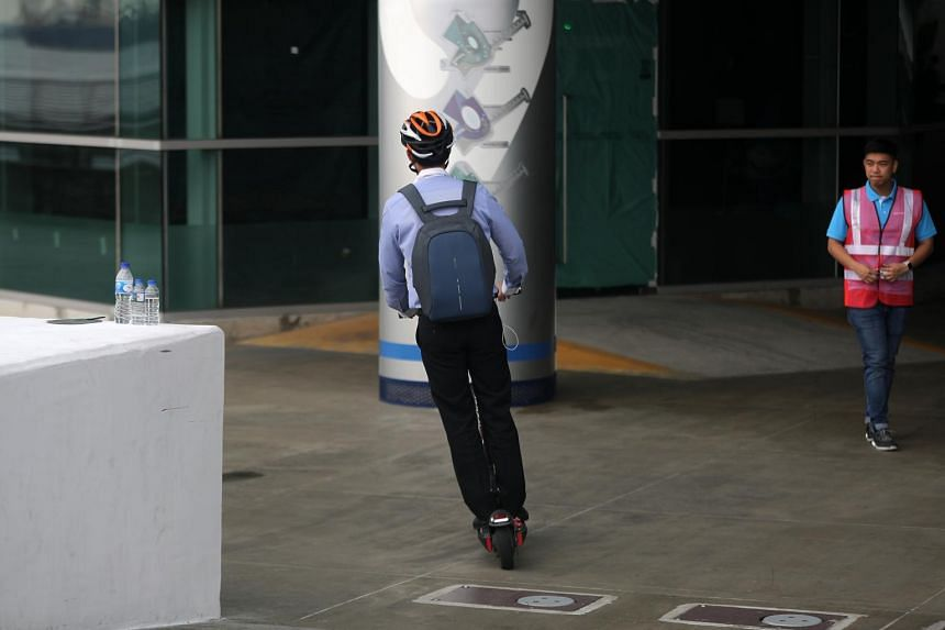 A man wearing a safety helmet rides his electric scooter at Marina Barrage.