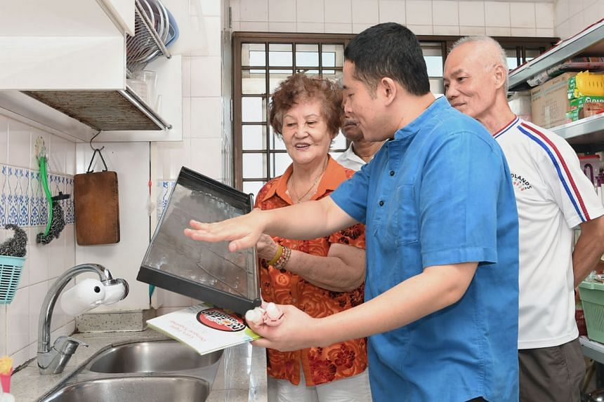 Senior Parliamentary Secretary for Home Affairs and Health Amrin Amin (in blue shirt) sharing tips on removing mosquito-breeding sources with Madam Kung Ah Lor during a home visit yesterday in Woodlands as part of the NEA's dengue prevention outreach