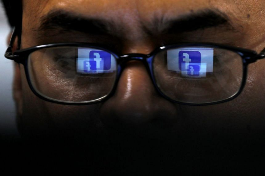 Facebook's logo is reflected in glasses in this picture illustration.