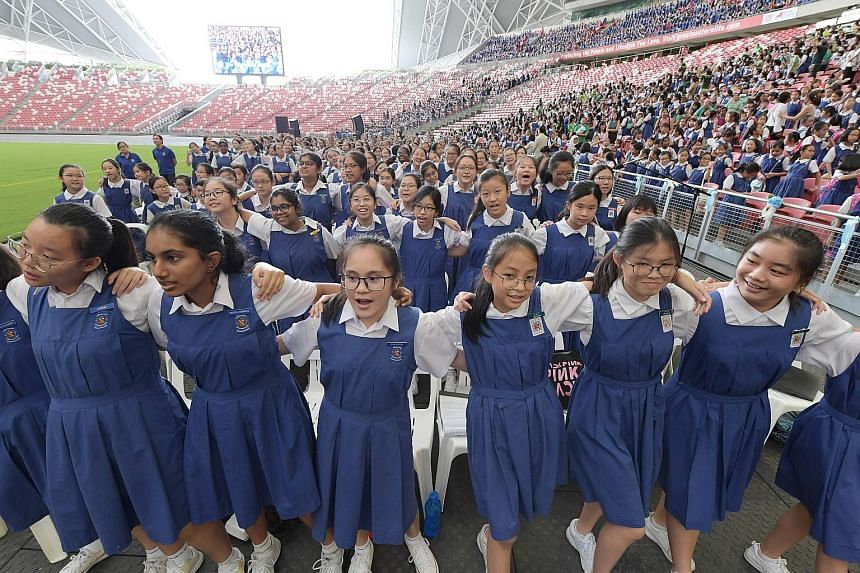 CHIJ schools celebrating their 165th anniversary at the National Stadium yesterday. The event drew 18,000 students, past and present, and included a thanksgiving mass led by Archbishop William Goh. ST PHOTOS: ALPHONSUS CHERN