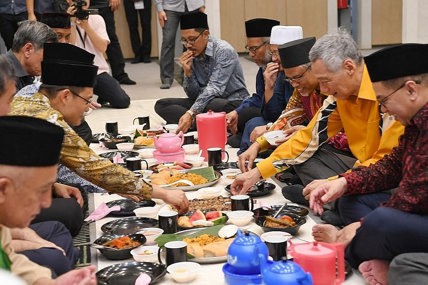 Prime Minister Lee Hsien Loong at the break-fast session at Masjid Alkaff Upper Serangoon. He was flanked by the mosque's executive chairman Kassim Kamis (right) and Minister-in-charge of Muslim Affairs Masagos Zulkifli. Muis chief executive Esa Maso