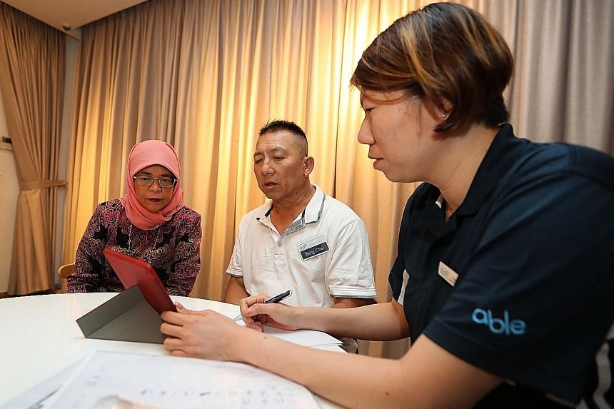Mr Mohamad Zahir, 27, who has a form of muscular dystrophy, flanked by physiotherapists Emily Ang and Mary Wrixton as he worked on his rehabilitation exercises.