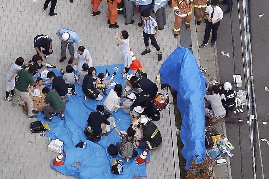 Rescue workers and police officers tending to victims at the scene of the attack in Kawasaki city, just outside Tokyo, yesterday. Two people - an 11-year-old girl and a 39-year-old man - were killed and 16 others injured when a man went on a rampage