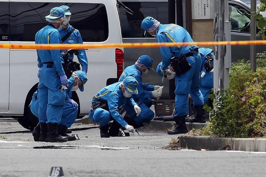 Top: Police at the scene where a knife-wielding attacker killed an 11-year-old schoolgirl and a man before taking his own life yesterday. The rampage outside Tokyo also left more than a dozen people injured. Left: A woman paying her respects to the v