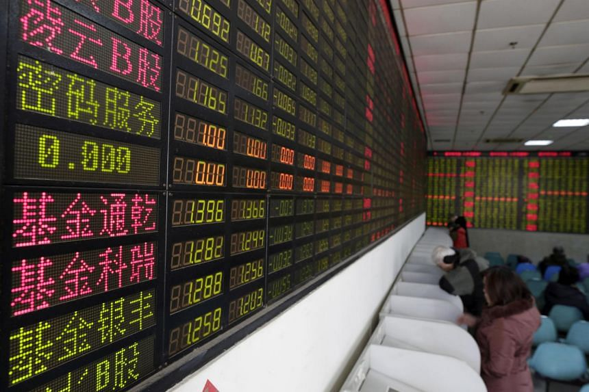 Investors looking at computer screens showing stock information in Shanghai, China.