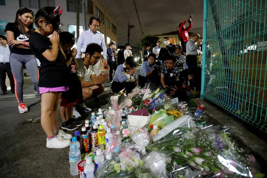 Local residents pray to mourn victims at the site where a stabbing occurred in Kawasaki, Japan, on May 28, 2019.