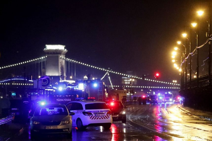 Police and fire brigade vehicles are seen on the Danube bank after a tourist boat capsized.