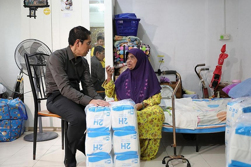 Dr Maliki Osman, Senior Minister of State for Defence and Foreign Affairs, visiting Madam Maimunah Hussin, 72, at her home in Bedok yesterday. Madam Maimunah is one of 500 beneficiaries in the South East District who received adult diapers through Pr