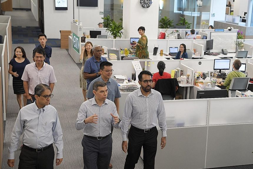Straits Times editor Warren Fernandez (centre) leading a tour of the recently revamped newsroom during a visit yesterday by Workers' Party leaders (from left) Leon Perera, Daniel Goh and Pritam Singh.