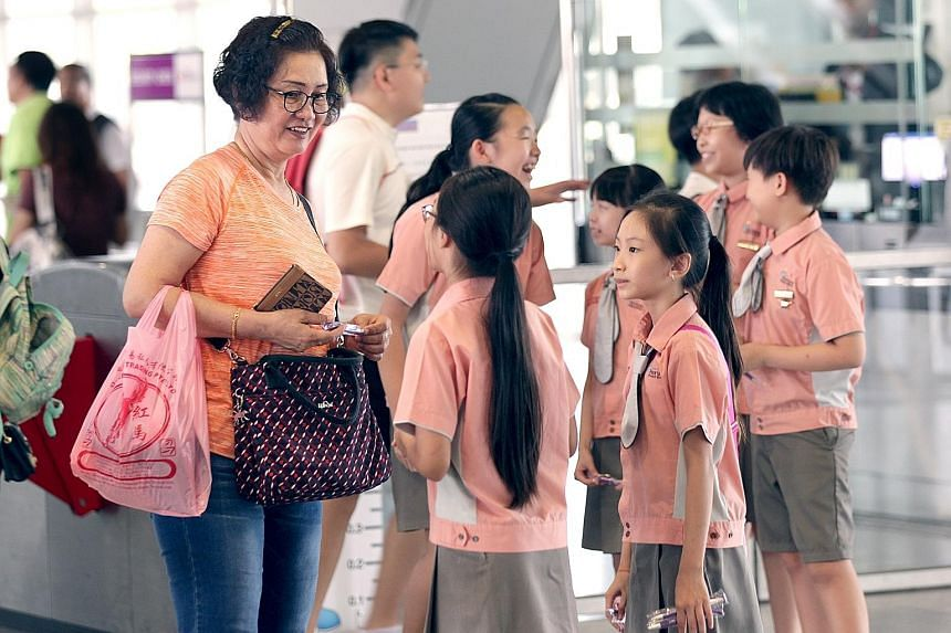 Horizon Primary School pupils interacting with a commuter at the Punggol MRT station yesterday, as part of an event to promote kindness and graciousness. The event was held in conjunction with the SBS Transit Kindness Month, and took place over two s