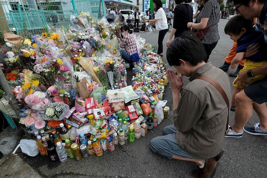 A man praying yesterday at the scene of the attack, where flowers and other tributes to those killed were laid. The rampage on Tuesday morning killed two people and injured 17 others, mainly young children. The 51-year-old attacker died after stabbin