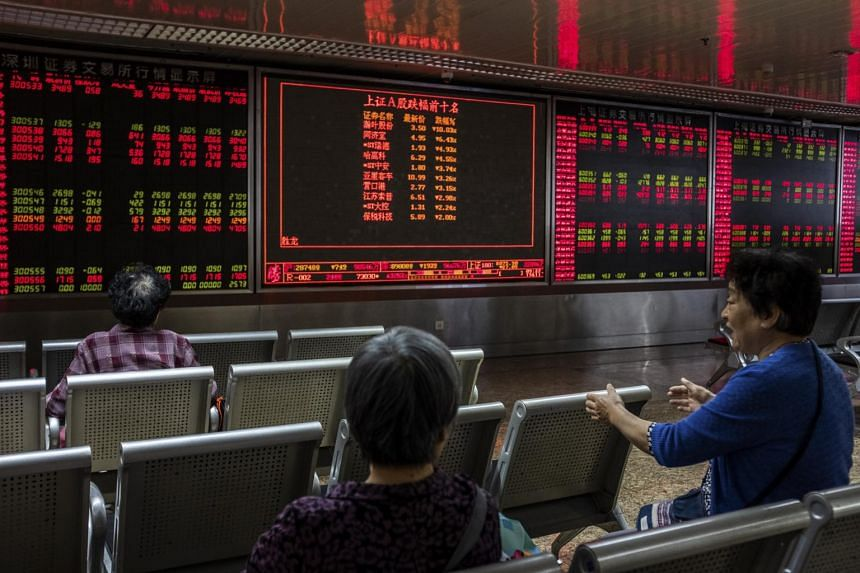 Screens showing stock market movements at a securities company in Beijing, China, on May 20, 2019.