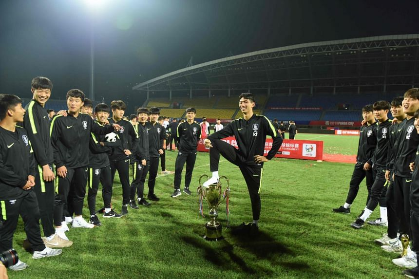 One of South Korea's victorious under-18 footballers with his foot on the Panda Cup following his team's victory.