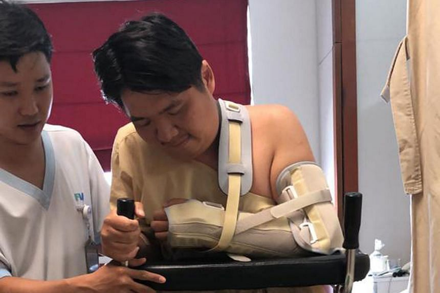 Mr Poh Wei Ye undergoing physiotherapy at the FV Hospital in Ho Chi Minh on May 30 after getting into an accident where he dislocated his left hand and broke his left leg.